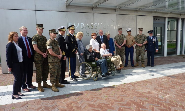 The two veterans being welcomed by Ambassador Hoekstra and Embassy staff members to the Embassy.